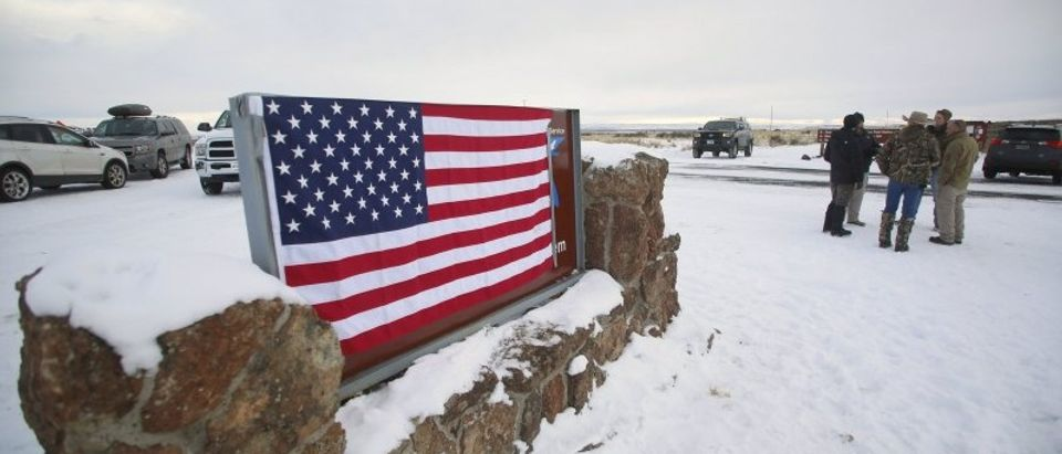 A U.S. flag covers a sign at the entrance of the Malheur National Wildlife Refuge near Burns