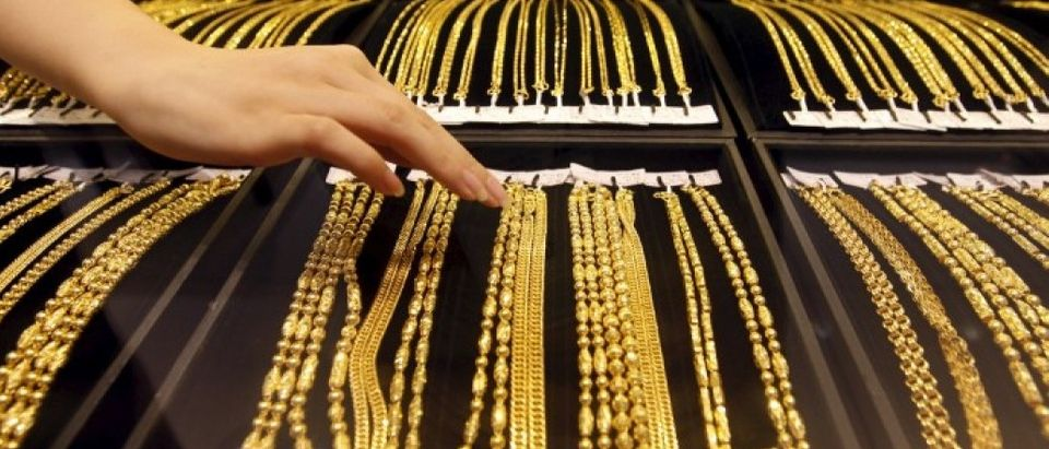File photo of an employee arranging gold jewellery in the counter as her arm is reflected in the mirror at a gold shop in Wuhan
