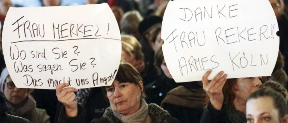 "Women hold up placards that read ""Mrs. Merkel: Where are you? What are you saying? This worries us!"" and ""Thanks (Cologne mayor Henriette) Reker!! Poor Cologne"" (R) during a protest in front of the Cologne Cathedral, Germany, January 5, 2016. REUTERS/Wolfgang Rattay"