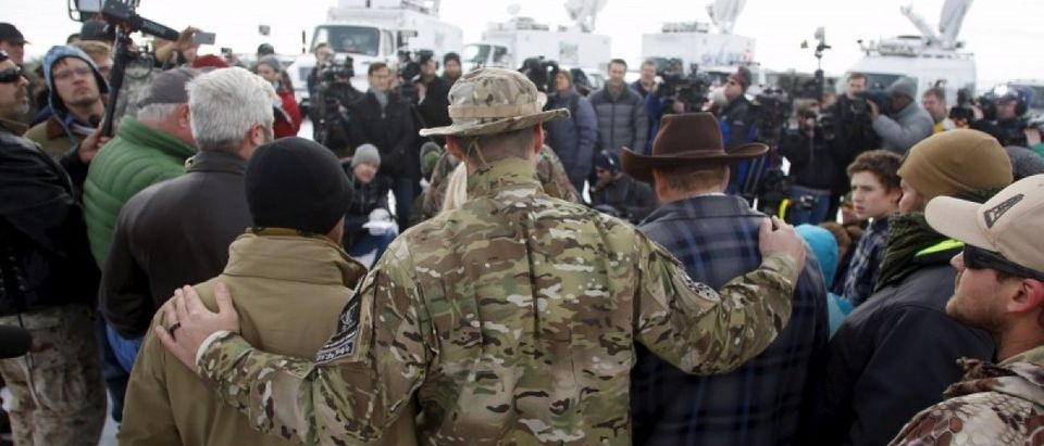 Militiamen embrace along with Ammon Bundy, after Bundy spoke to the media at the Malheur National Wildlife Refuge near Burns, Oregon