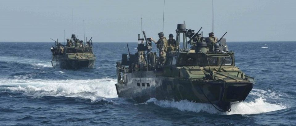 U.S. Navy handout photo of a riverine patrol boat from Costal Riverine Squadron 2 escorts the guided-missile cruiser USS Bunker Hill while in the Arabia Gulf