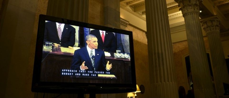 U.S. President Obama is seen on a television screen placed in the hallway outside the U.S. House of Representatives chamber in Washington