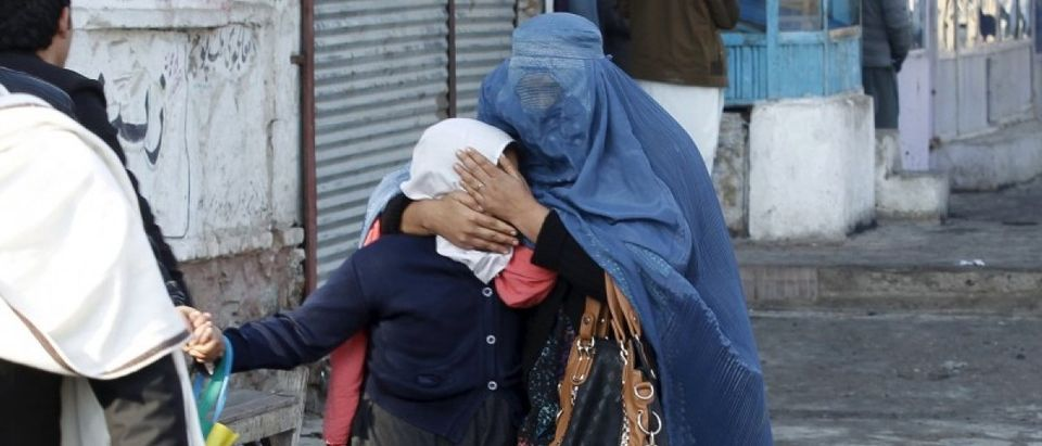 A woman holds her daughter's head as they walk away after a blast near the Pakistani consulate in Jalalabad