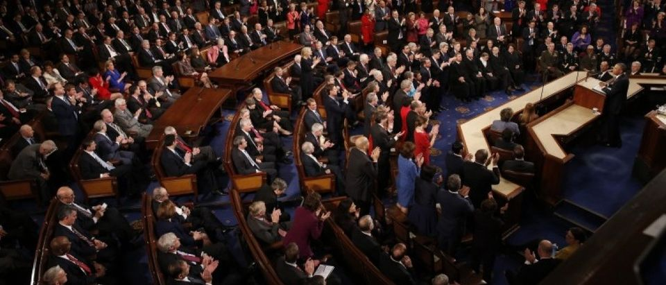 Democratic members of Congress rise to their feet for a standing ovation as Republican members remain seated during U.S. President Obama's State of the Union address to a joint session of Congress in Washington