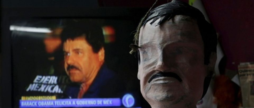 "A pinata in progress depicting the drug lord Joaquin ""El Chapo"" Guzman is seen in front of a television showing a news bulletin of him at a workshop in Reynosa"