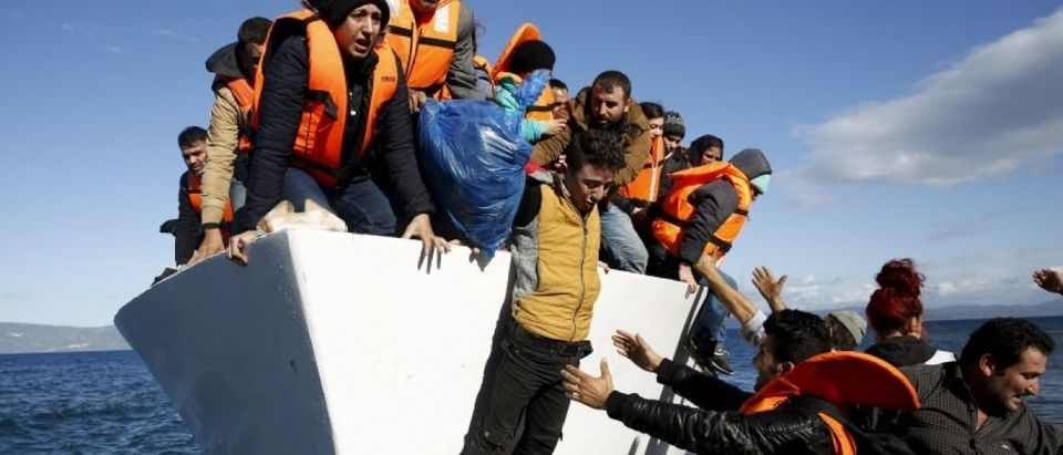 File photo of refugees and migrants jumping off a boat as they arrive on the Greek island of Lesbos
