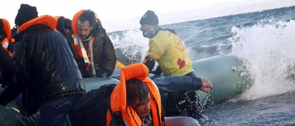A refugee tries to stand up after falling into the sea as Syrian and Iraqi refugees arrive on a raft on a beach on the Greek island of Lesbos