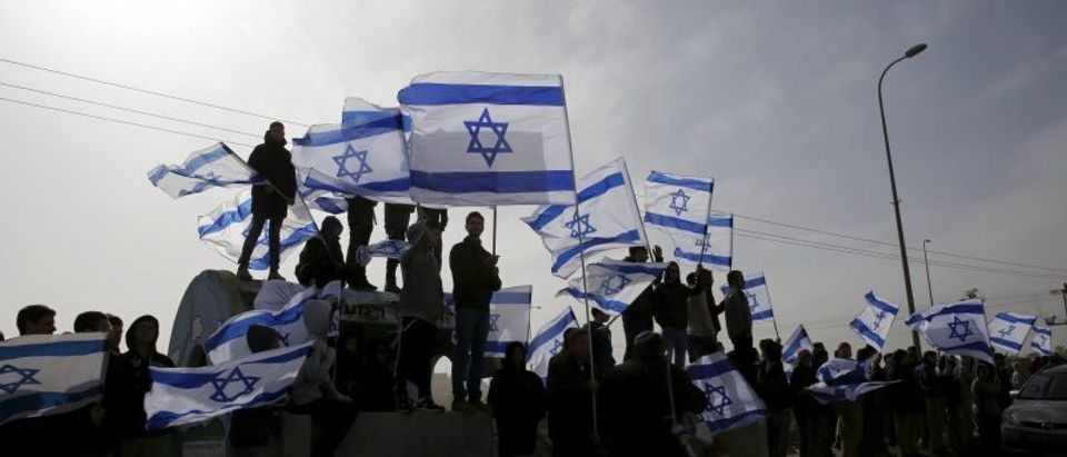 Israelis wave their national flag as a convey transporting the body of Dafna Meir passes on its way to a cemetery, near the West Bank Jewish settlement of Efrat
