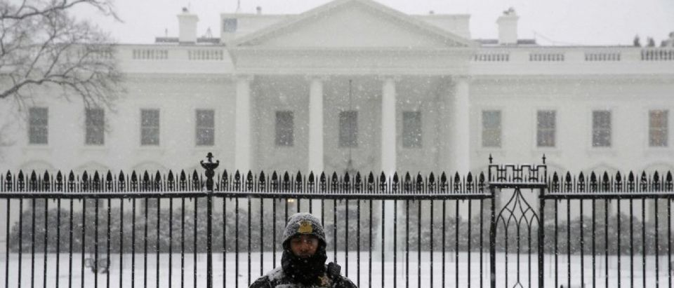 A uniformed Secret Service officer stands in the freshly fallen snow outside the White House after snowstorm arrived in Washington