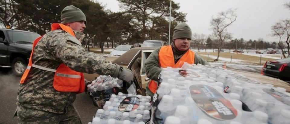Michigan National Guard members help to distribute water to a line of residents in their cars in Flint, Michigan