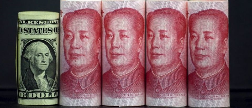 File picture illustration taken in Beijing, China shows Chinese 100 yuan banknotes and a U.S. one dollar banknote