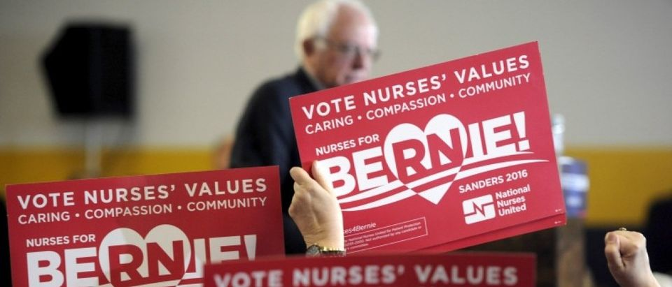 Supporters from the Nurses for Bernie Super PAC wave signs as U.S. Democratic presidential candidate Sanders speaks at a campaign event in Des Moines, Iowa