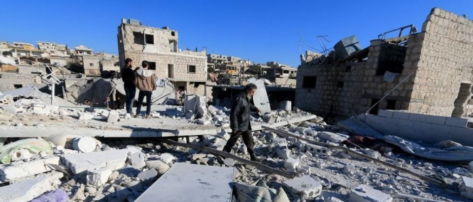 People inspect a site hit by what residents said were airstrikes carried out by the Russian air force in the town of Turmanin