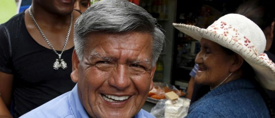Peruvian presidential candidate Cesar Acuna greets supporters during a rally at a market in Brena district of Lima