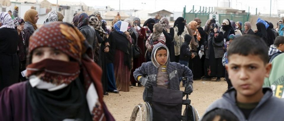 Syrian refugees stand in line as they wait for aid packages at Al Zaatari refugee camp