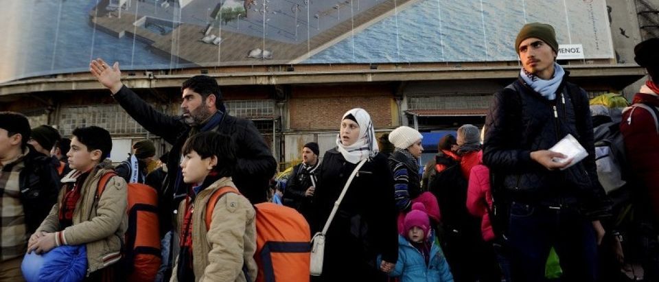 Refugees and migrants walk after disembarking from the passenger ferry Blue Star1 at the port of Piraeus, near Athens