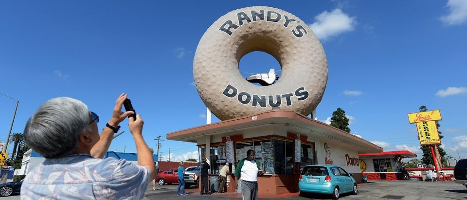 A man takes a picture with his mobile phone of a toy space shuttle placed in the donut hole of Randy's Donuts in preparation of the ground transport of the space shuttle Endeavour on October 10, 2012 in Los Angeles, California. (Kevork Djansezian/Getty Images)