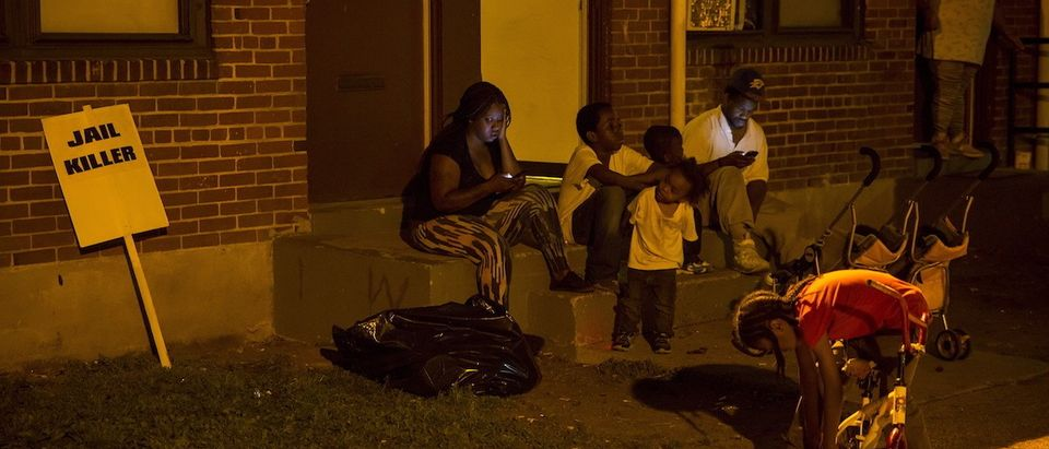 People are seen at the Gilmor Homes housing projects in Baltimore, Maryland