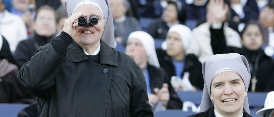 Sister Peyton uses pair of binoculars next to Sister Horseman in the stadium before Pope Benedict XVI conducts Mass in Washington