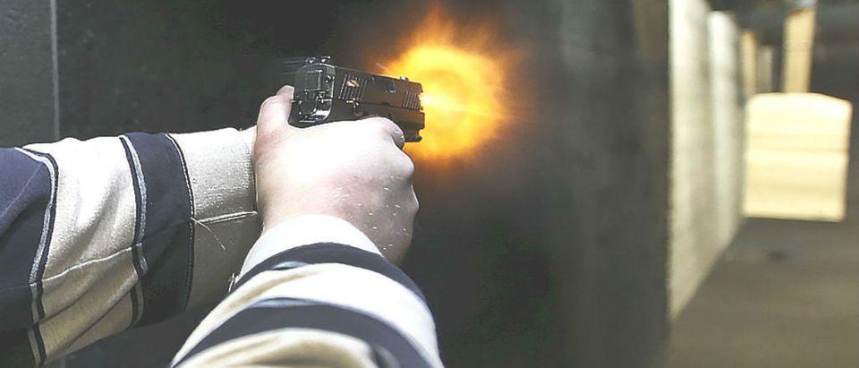 Flames exit the barrel of a gun as a man fires a Sig P320 handgun at the Ringmasters of Utah gun range, in Springville, Utah on December 18, 2015. REUTERS/George Frey
