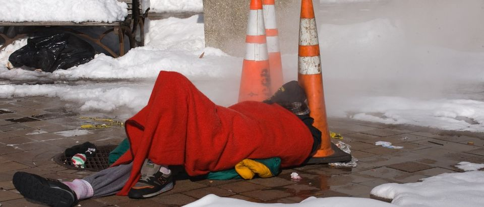 A homeless man sleeps next to a steaming
