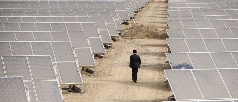 A man walks through solar panels at a solar power plant under construction in Aksu