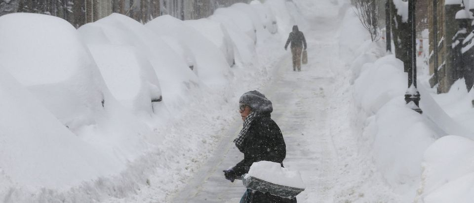 Woman shovels snow on Joy Street during a winter blizzard in Boston