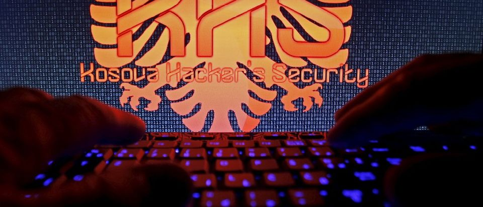 "A man types on a keyboard in front of the logo of ""Kosova Hackers Security"" in this photo illustration taken in Sarajevo"