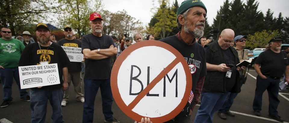 A Sugar Pine Miner supporter holds a anti-BLM sign at a rally outside the Bureau of Land Management's offices in Medford