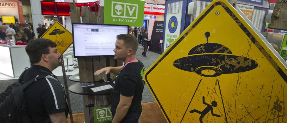 Alien abduction warning signs are posted in the AlienVault booth during the Black Hat USA 2015 cybersecurity conference in Las Vegas