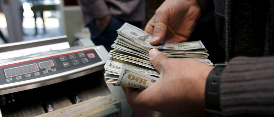A man counts wads of U.S. dollars on a money counting machine at a currency exchange shop in Baghdad