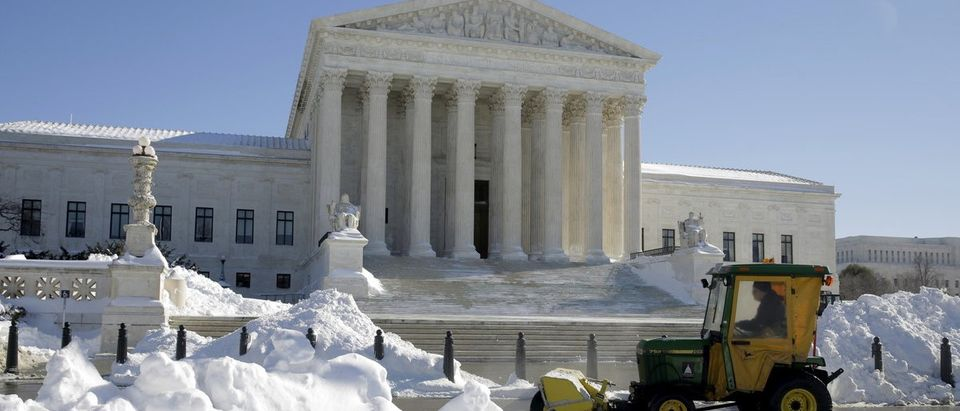 A man uses a sweeper to clear snow from in front of the Supreme Court after a major winter storm swept over Washington