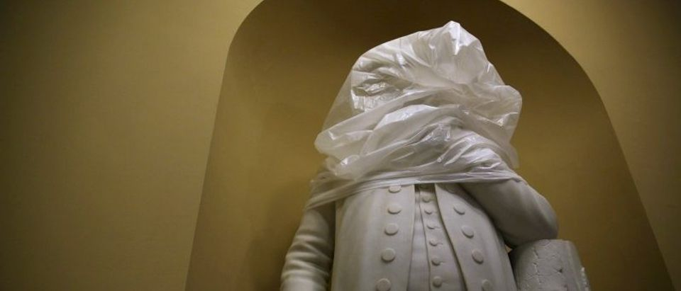 The statue of Franklin is covered with plastic during construction in an empty hallway outside the U.S. Senate at the U.S. Capitol in Washington