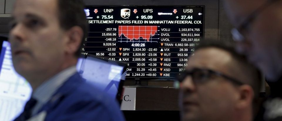 Traders work at a post as a screen shows the Dow Jones Industrial Average after the closing bell on the floor of the New York Stock Exchange