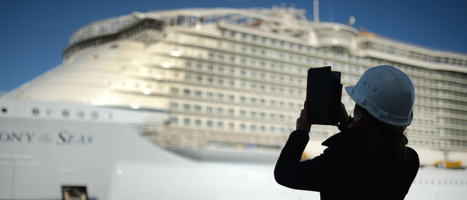 A woman takes a picture with a tablet of the Harmony of the Seas cruise ship still under construction at the STX shipyard of Saint-Nazaire, western France, on February 18, 2016. (JEAN-SEBASTIEN EVRARD/AFP/Getty Images)