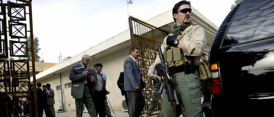 A foreign security contractor stands gua