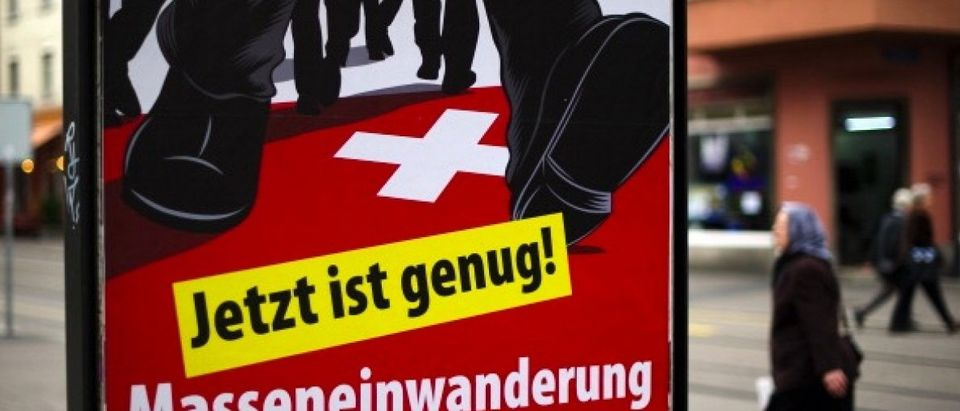 A woman walks past a poster of the far-right Swiss People's Party depicting the legs of men wearing suits marching across the Swiss flag and bearing the slogan 'That's enough. Stop mass immigration!' on October 13, 2011 in Kleinbasel (Little Basel) a neighborhood of Basel, northern Switzerland. Switzerland will head to the polls on October 23, 2011 to elect a new parliament, with the far-right expected to gain ground on the back of fears over immigration and the impact of the eurozone's public debt crisis. AFP PHOTO / FABRICE COFFRINI (Photo credit should read FABRICE COFFRINI/AFP/Getty Images)
