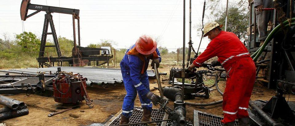 Men work at an oil pump in Lagunillas, Ciudad Ojeda