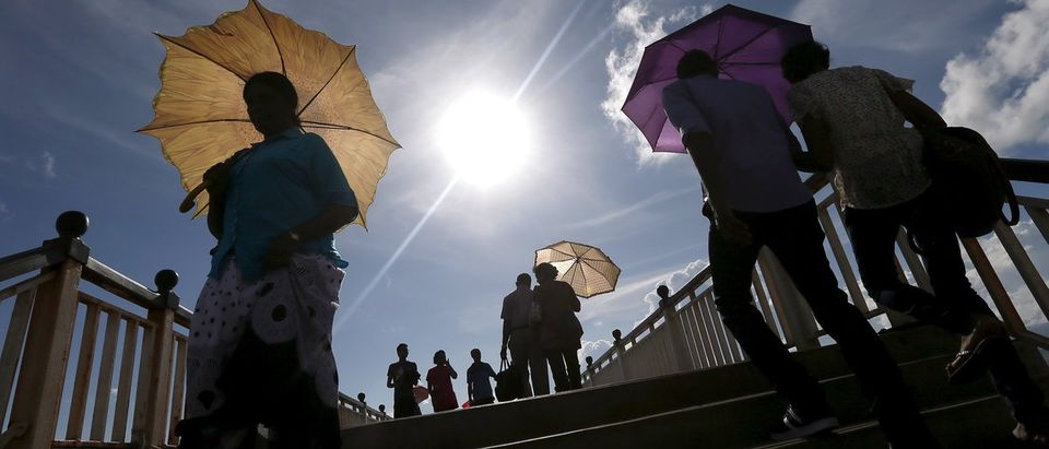 People hold their umbrellas as they walk on a bridge on a hot day at Galle Face Green in Colombo