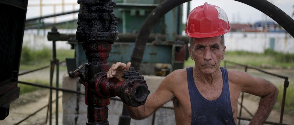 A technician of Cuba's state-run CUPET poses for a picture near an oil pump in Mayabeque province