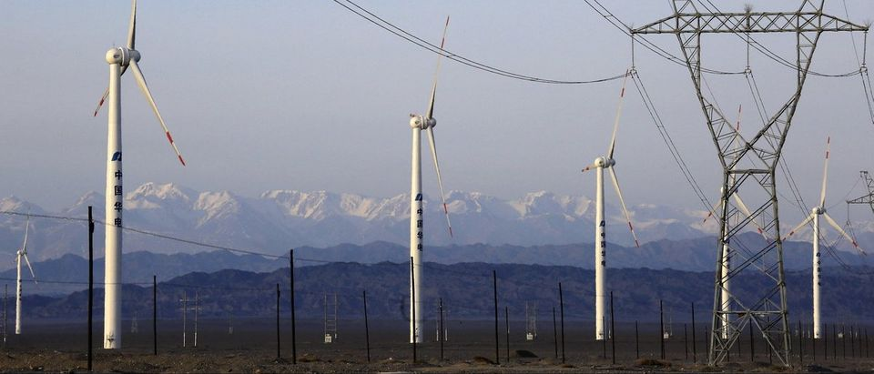 An electricity pylon is seen next to wind turbines at a wind power plant in Hami