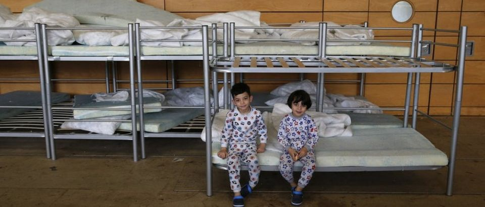 Migrant children from Iraq sit on beds inside the sports hall of the Jane-Addams high school transformed into a refugee shelter in Berlin's Hohenschoenhausen district