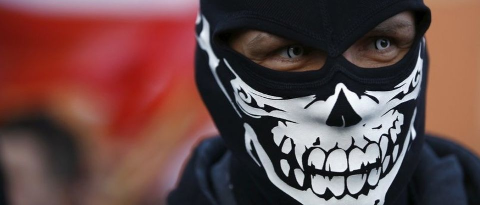 A protester wearing a mask looks on during an anti-immigrant rally in front of the Royal Castle in Warsaw