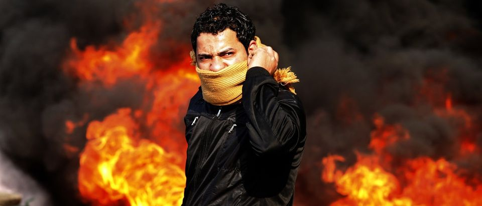 A protester stands in front of a burning barricade during a demonstration in Cairo January 28, 2011. Police and demonstrators fought running battles on the streets of Cairo on Friday in a fourth day of unprecedented protests by tens of thousands of Egyptians demanding an end to President Hosni Mubarak's three-decade rule. REUTERS/Goran Tomasevic
