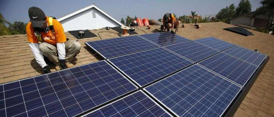 File photo of Vivint Solar technicians installing solar panels on the roof of a house in Mission Viejo