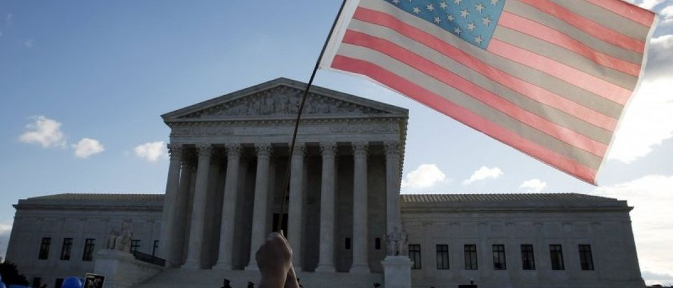 A protester holds up a flag in front of the U.S. Supreme Court in Washington