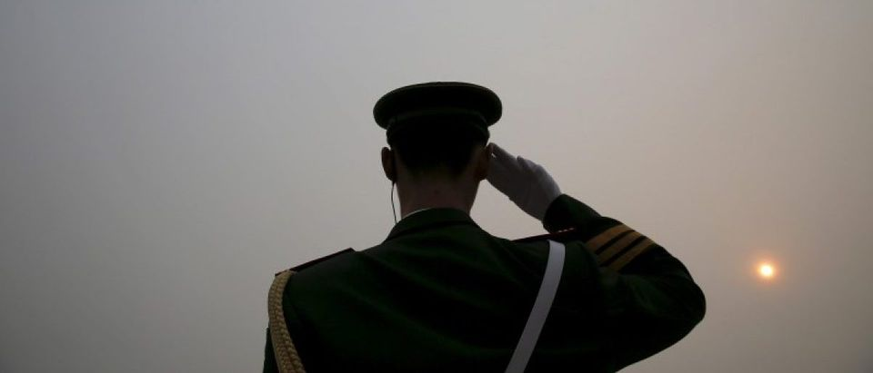 The sun is seen through smog on a severely polluted day as a paramilitary policeman salutes to delegates arriving to the Great Hall of the People ahead of Saturday's opening ceremony of the National People's Congress (NPC), in Beijing