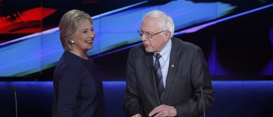 Democratic U.S. presidential candidates Clinton and Sanders talk during a commercial break at the Democratic U.S. presidential candidates' debate in Flint