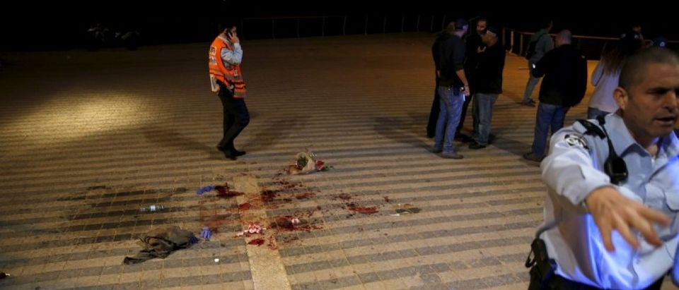 An Israeli policeman clear the spot where, according to Israeli police spoksperson, at least 10 Israelis were stabbed, in the popular Jaffa port area of Tel Aviv, Israe