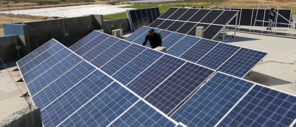 A Palestinian worker installs solar panels atop the roof of a medical centre in Gaza City